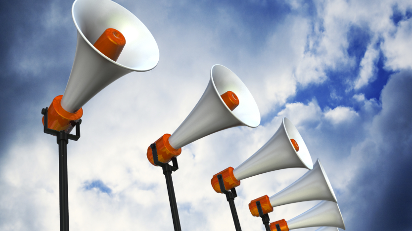 Megaphone speakers in a row with sky background